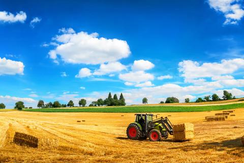 Traktor beim Laden von Stroh