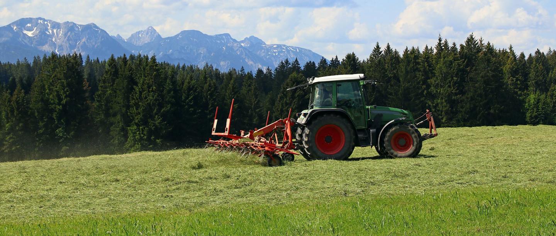 Bauer mäht im Sommer die Allgäuer Wiesen mit seinem Traktor