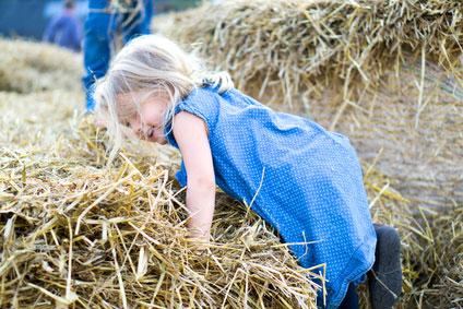 Mädchen spielt im Stroh