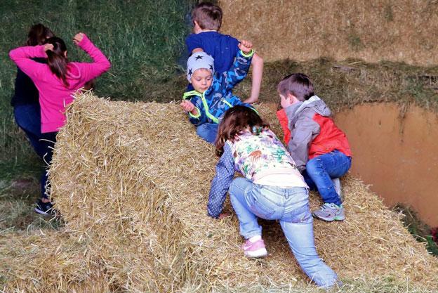 Kinder spielen im Stroh am Bio Berghof Kinker